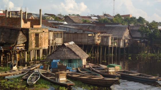 Fotografia z Requeny: łodzie na tle prowizorycznych budynków, fot. Łukak Krokoszyński